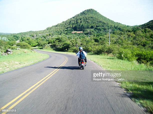 Rear View Full Length Of Woman Riding Motorcycle Against Mountain
