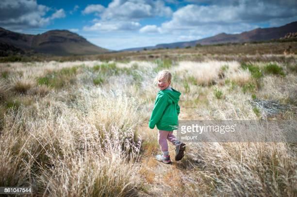 Fille de vue arrière de randonnée dans une nature magnifique regarder par-dessus l'épaule gauche