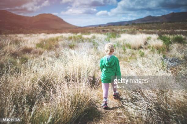 Fille de vue arrière randonnée entre-deux longues herbes