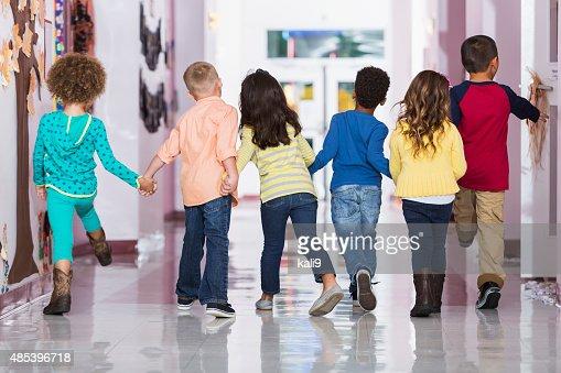 Rear view, group of preschoolers walking down hallway