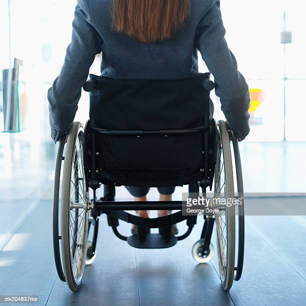 rear view mid section of a businesswoman sitting in a wheelchair in an office