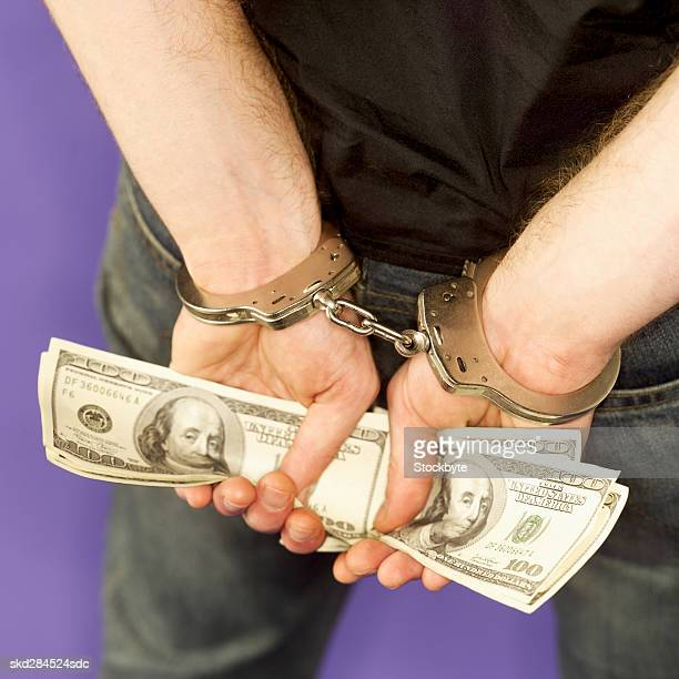 Rear view mid section of man's hands in handcuffs and holding American dollar notes