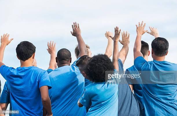 Rear view multi-ethnic group of volunteers raising hands