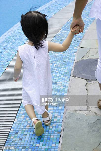 Rear view of a baby girl walking with her mother at the poolside