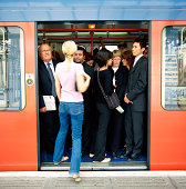 Rear View of a Blonde Woman Stepping Onto a Crowded Commuter Train