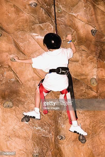 Rear view of a boy climbing a wall