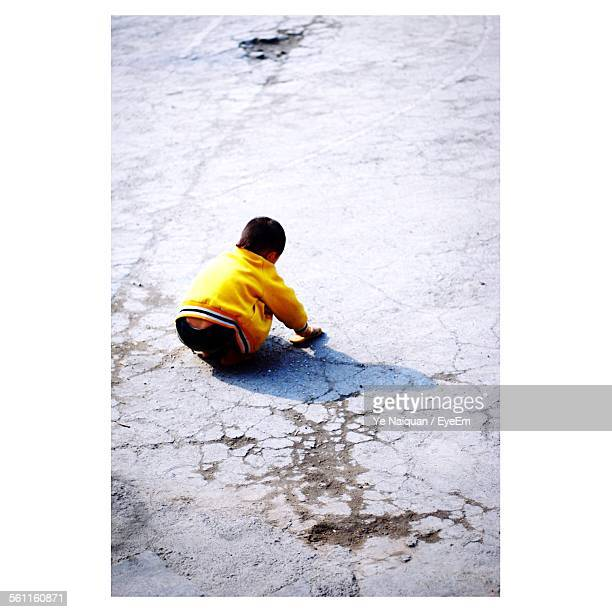 Rear View Of A Boy Crouching On Street