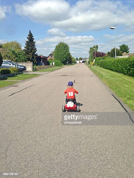 Rear view of boy (2-3) cycling on road