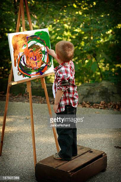 Rear view of a boy finger painting on a canvas in the park