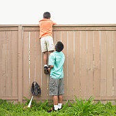 Rear view of a boy helping another boy climbing a fence