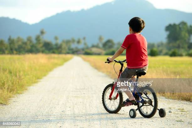 Rear view of a boy leaning cycling