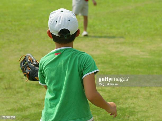 Rear view of a boy playing catch in a field