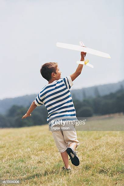 Rear View of a Boy Running in a Field Holding a Toy Aircraft