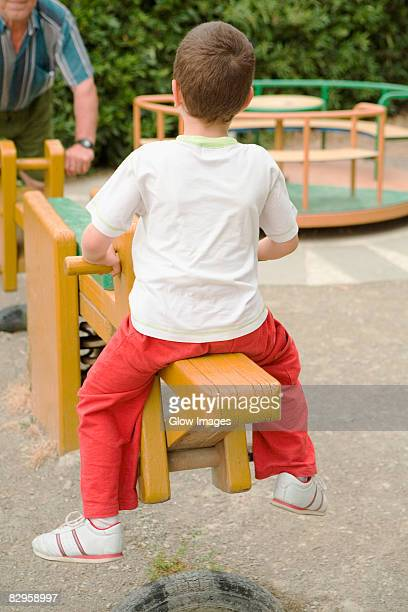 Rear view of a boy sitting on a seesaw in a park, Cinque Terre, Manarola, La Spezia, Liguria, Italy