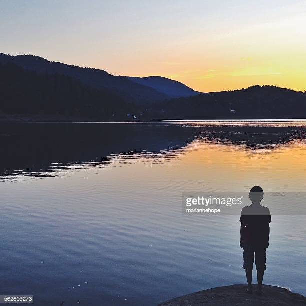 Rear view of a boy standing on a rock at sunset, Hof, Norway