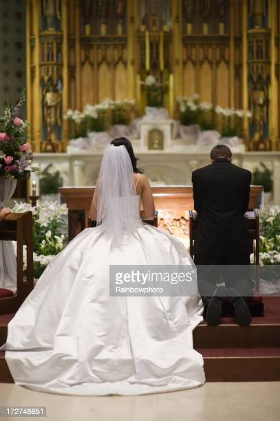 Rear view of a bride and groom kneeling at altar at wedding