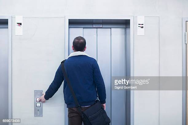 Rear view of a businessman pressing elevator button in an office, Freiburg im Breisgau, Baden-Württemberg, Germany