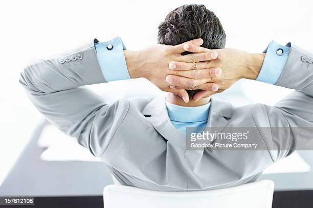 Rückansicht des ein Geschäftsmann, sitzen mit Händen hinter dem Kopf
