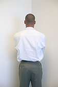 Rear view of a businessman standing facing the wall