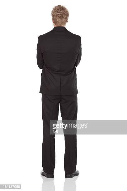 Rear view of a businessman standing with arms crossed