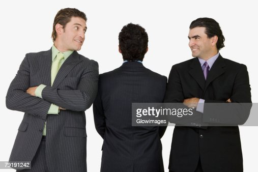 Rear view of a businessman standing with two businessmen with their arms crossed : Foto de stock