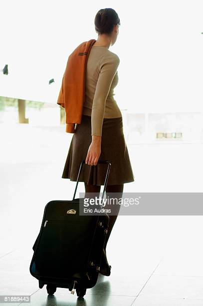 Rear view of a businesswoman pulling her luggage at an airport