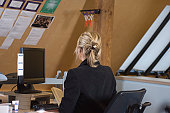 Rear view of a businesswoman sitting in front of a desktop PC
