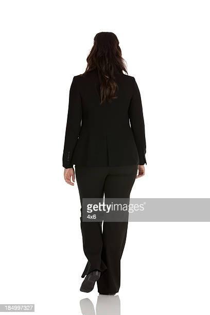 Vue arrière d'une femme d'affaires à pied