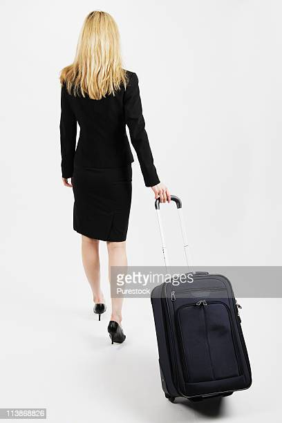 Rear view of a businesswoman walking with carry-on luggage