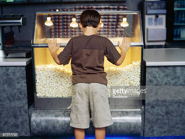 Rear view of a child looking inside a popcorn machine