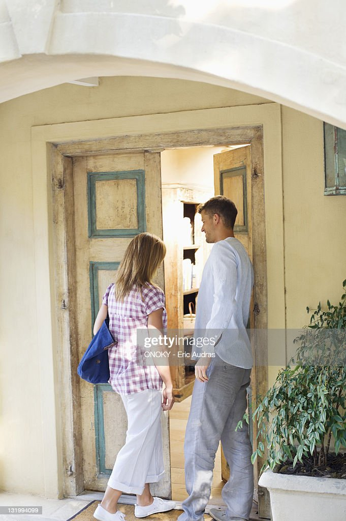 Rear view of a couple entering into house