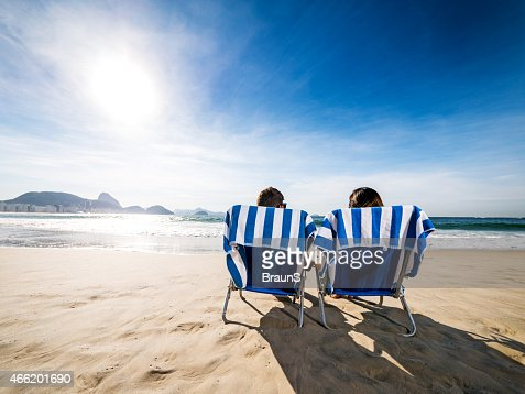 Rear view of a couple in deck chairs at beach.