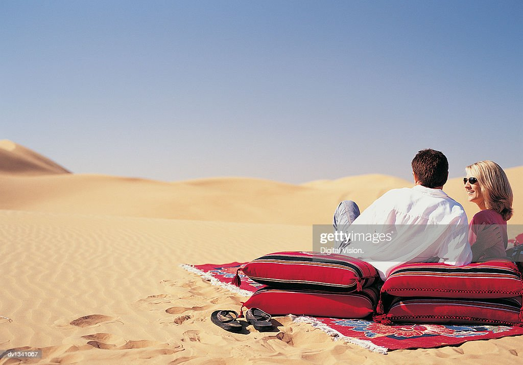 Rear View of a Couple Lying on a Blanket and Cushions Looking at the Desert View