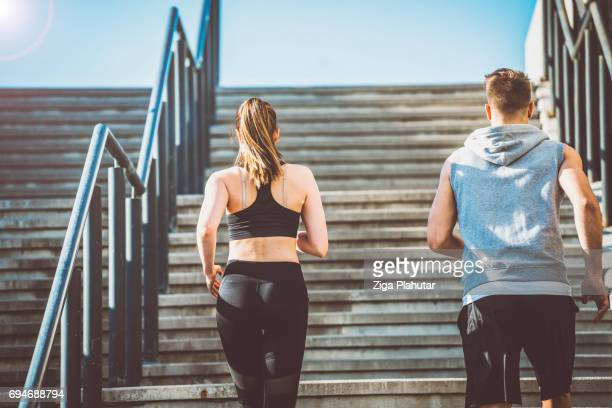 Rear view of a couple running up the stairs
