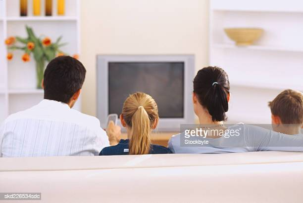 Rear view of a couple sitting on the couch in front of a television with their children (8-10)