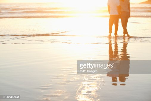 Rear view of a couple standing together on beach at sunset : Stock Photo