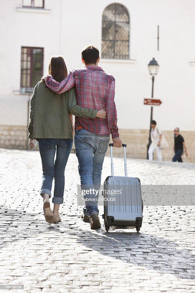 Rear view of a couple walking on a road with a suitcase, Paris, Ile-de-France, France