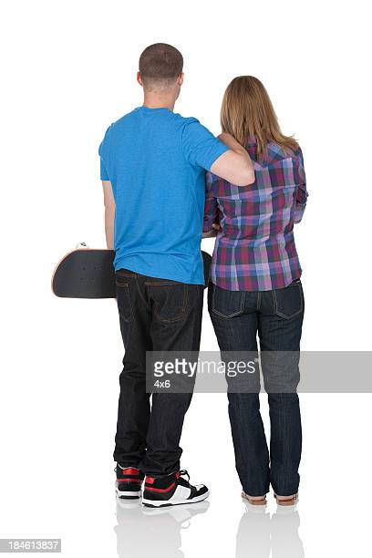 Rear view of a couple with skateboard