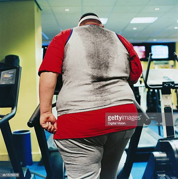 Rear View of a Fat Man Walking on an Exercise Machine in a Gym