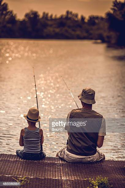 Rear view of a father and son fishing in freshwaters.