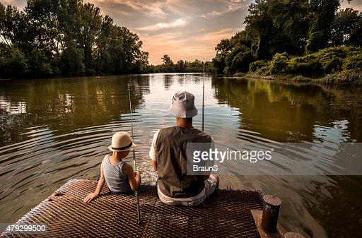 Vista traseira de um pai e seu filho pesca.