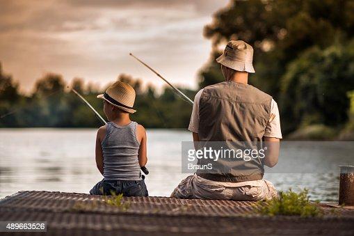 Vista traseira de um pai e seu filho pesca de água doce.