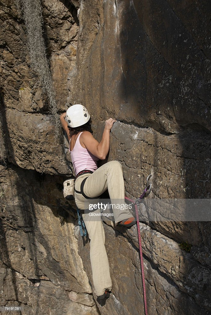 Rear view of a female rock climber scaling a rock face : Stock Photo
