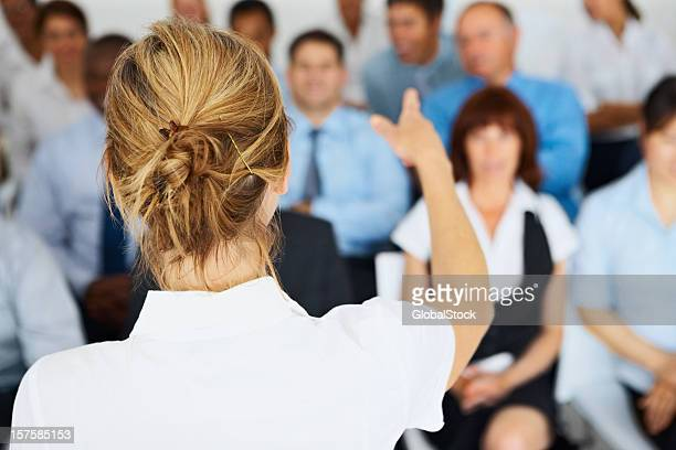 Rear view of a female speaker giving presentation to team