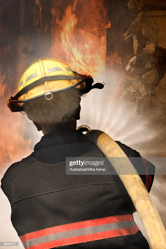 Rear View Of A Firefighter Carrying A Fire Hose On His ...