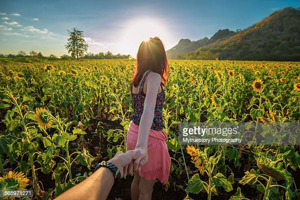 Rear view of a girl at the sunflower field