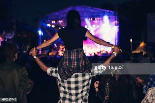 Rear view of a girl getting carried on a friends shoulders at the music festival.