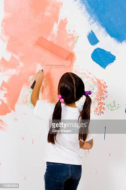 Rear view of a girl painting a wall with a paint roller