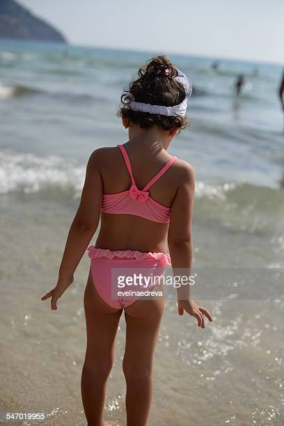 Rear view of a girl standing in the sea at the beach