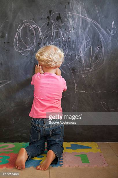Rear view of a girl writing on a blackboard